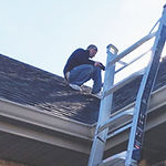 Image of man scaling a roof