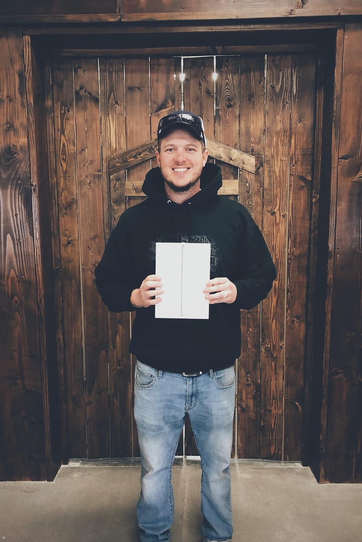 Image of man holding iPad in front of wood door