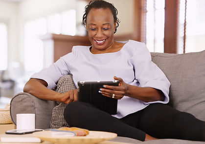 An elderly black woman uses her tablet while relaxing on the couch.jpg
