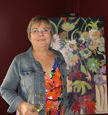 Terry Smith standing in front of one of her large flower paintings.