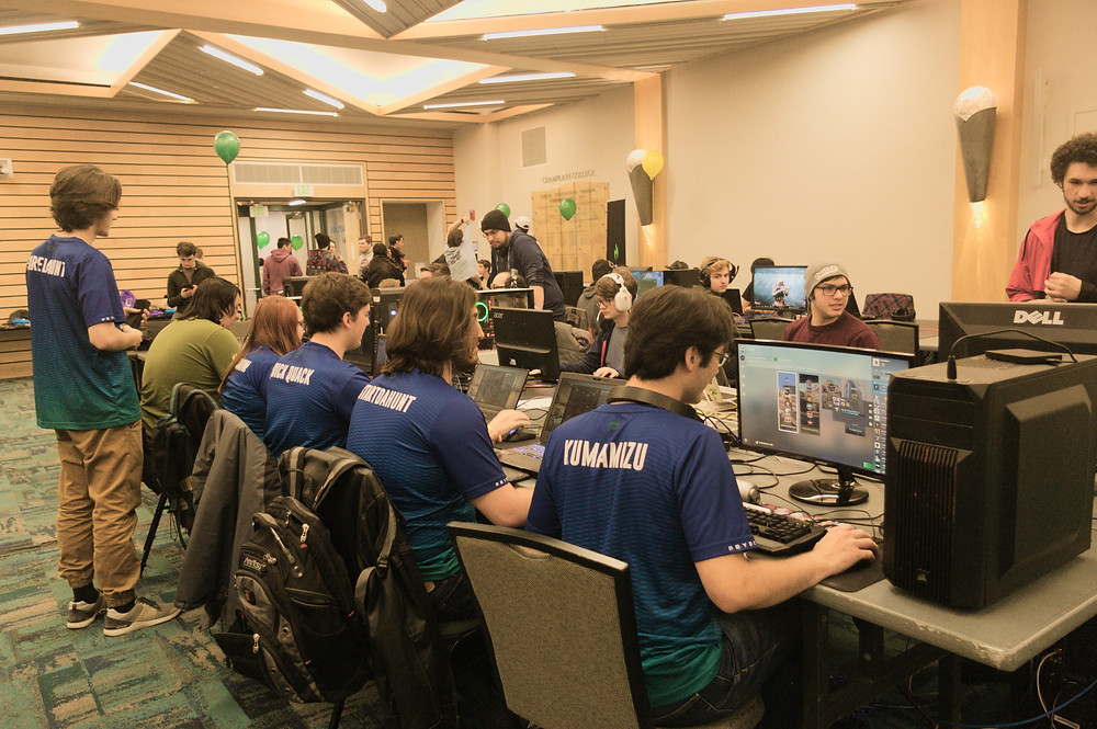 Various people sit in chairs in front of laptops, playing video games.  They are arranged in long tables, with balloon decorating the ends of the rows.