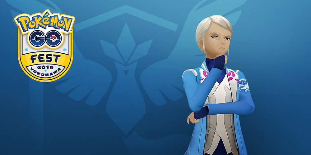 Team leader Blanche stands, looking directly at the camera with one arm crossed over their torso and the other resting under their chin. The Team Mystic logo is emblazoned on the blue background.
