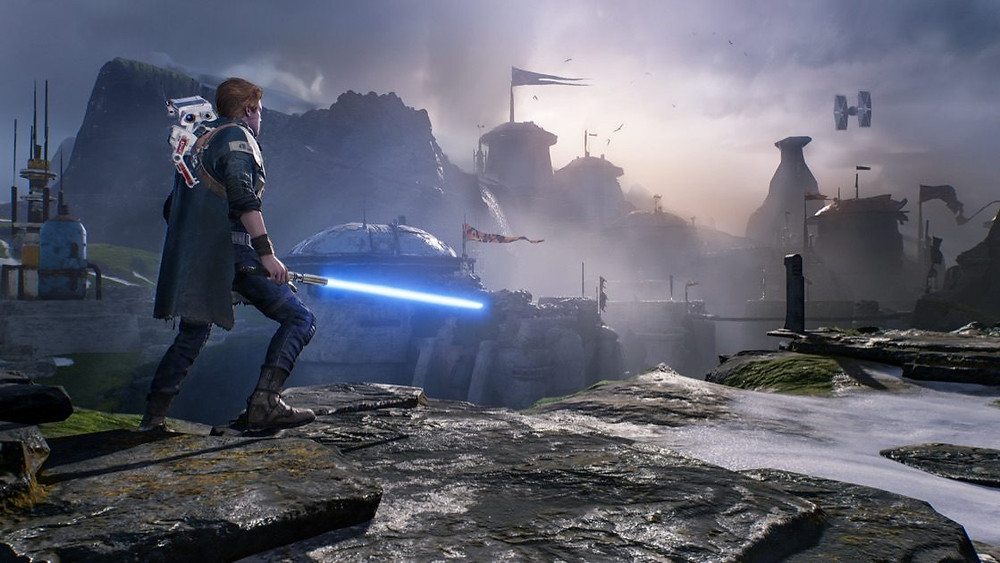 A character holding a light saber looks over a rocky terrain.  There are buildings in the distance.