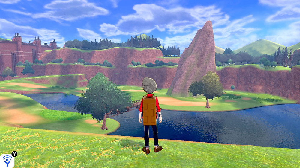 The main character, wearing a red shirt, black pants, a gray hat, and a brown backpack, stands looking at scenery.  They look over an edge at a small river flowing into a lake, and other edges nearby have rocks or trees.