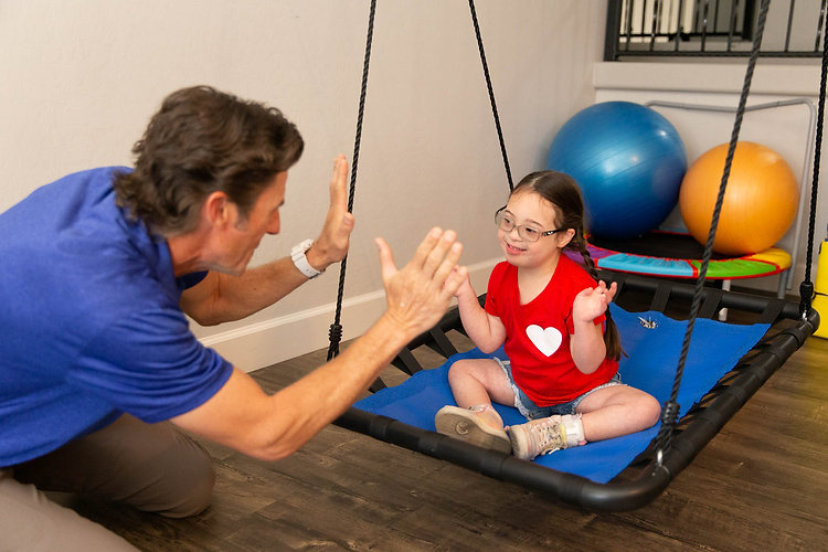 Therapist working with his young client in a sensory swing.
