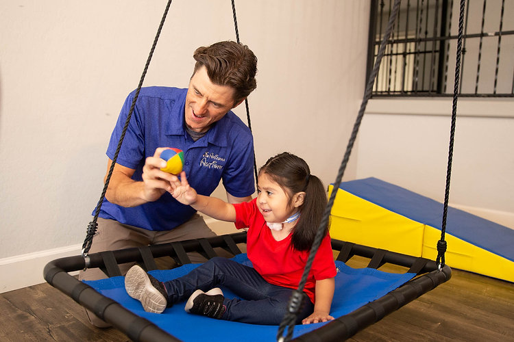 Provider and client working together with a sensory swing.