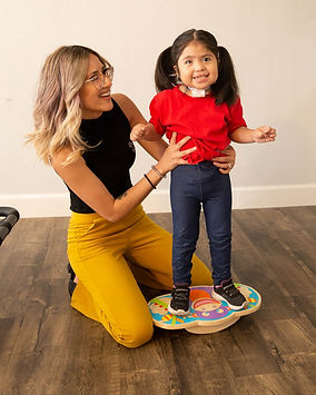 Happy, smiling Physical Therapist and her adorable client with special needs.