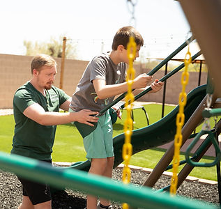 Respite Care Provider pushing his client on a swing.