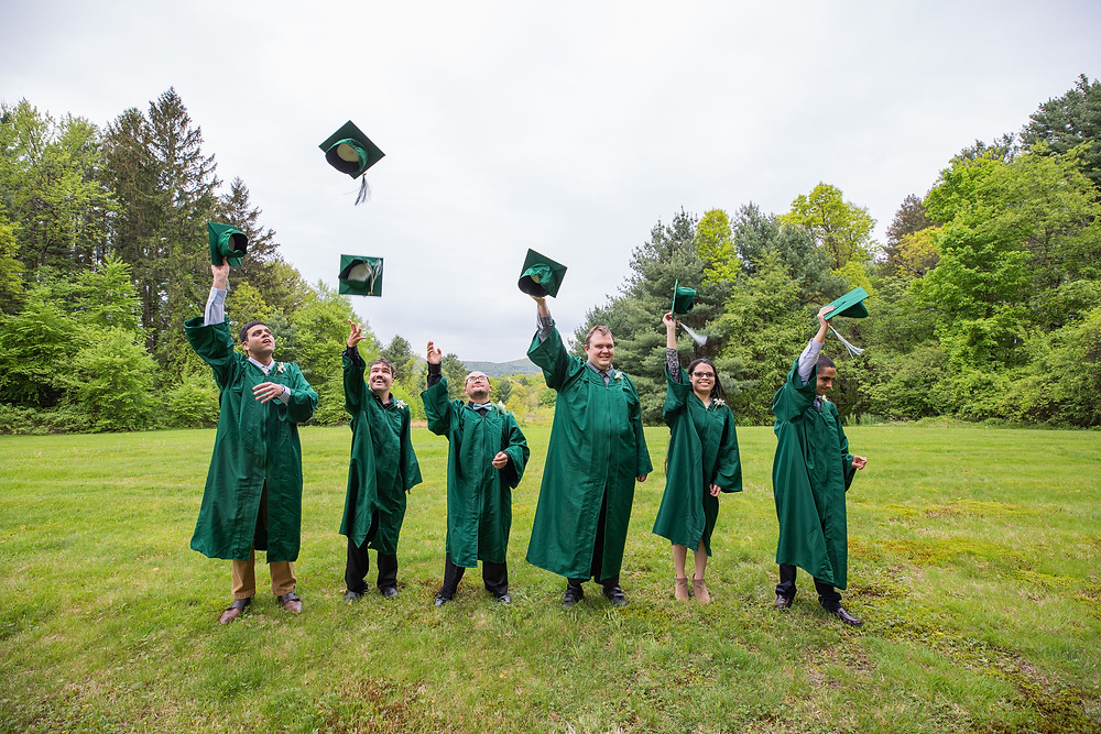 Image of the six graduates wearing green graduation gowns and throwing their caps in the air; a gray sky and lush green grass and foliage is visible in the background.