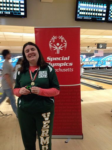 Image of Carly Golden, wearing her BHMA Kingpins green polo shirt, posing with her medal in front of the red Special Olympics pop-up sign at a bowling alley.
