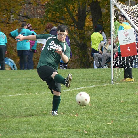 Image of Ben Krifka, wearing his green Bandits uniform, kicking the soccer ball with his right foot.