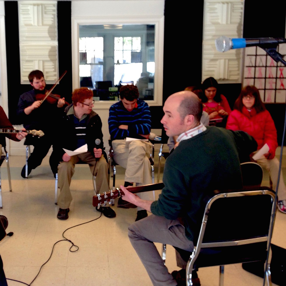 Image of Music Instructor playing the guitar and leading the American Roots Ensemble during rehearsal.