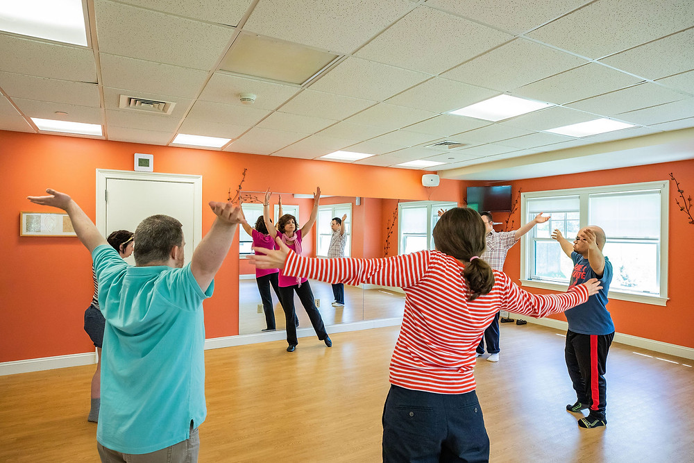 Image of five students and Dance Instructor Mary Ann Holmes in a circle with their arms open in the coral-colored dance studio.