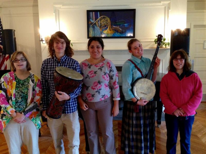 Image of five students posing with instruments in the Great Room.