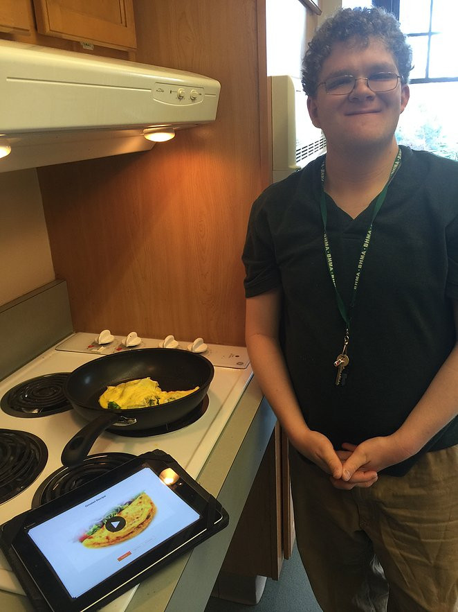 Image of Mark Palardy, wearing a black polo shirt and khakis, posing next to a stove with his completed omelette prepared with the help of assistive technology.