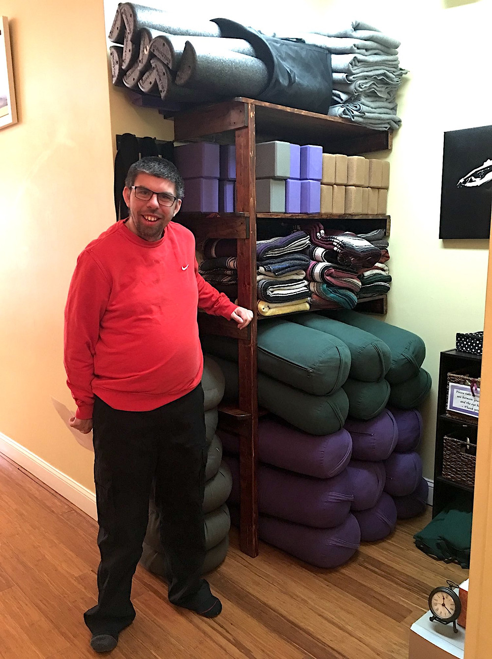 Photo of Joey Gagnon, wearing a red sweatshirt and black pants, posing in front of an organized shelf with bolsters, mats, and other yoga supplies.