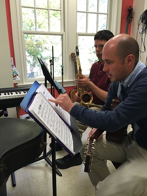 Image of Andy Anderson pointing at sheet music on a music stand as student John readies his saxophone in the red studio.