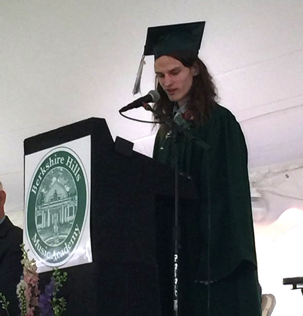 Image of Sasha, wearing his green graduation cap and gown, speaking at the on-stage podium.