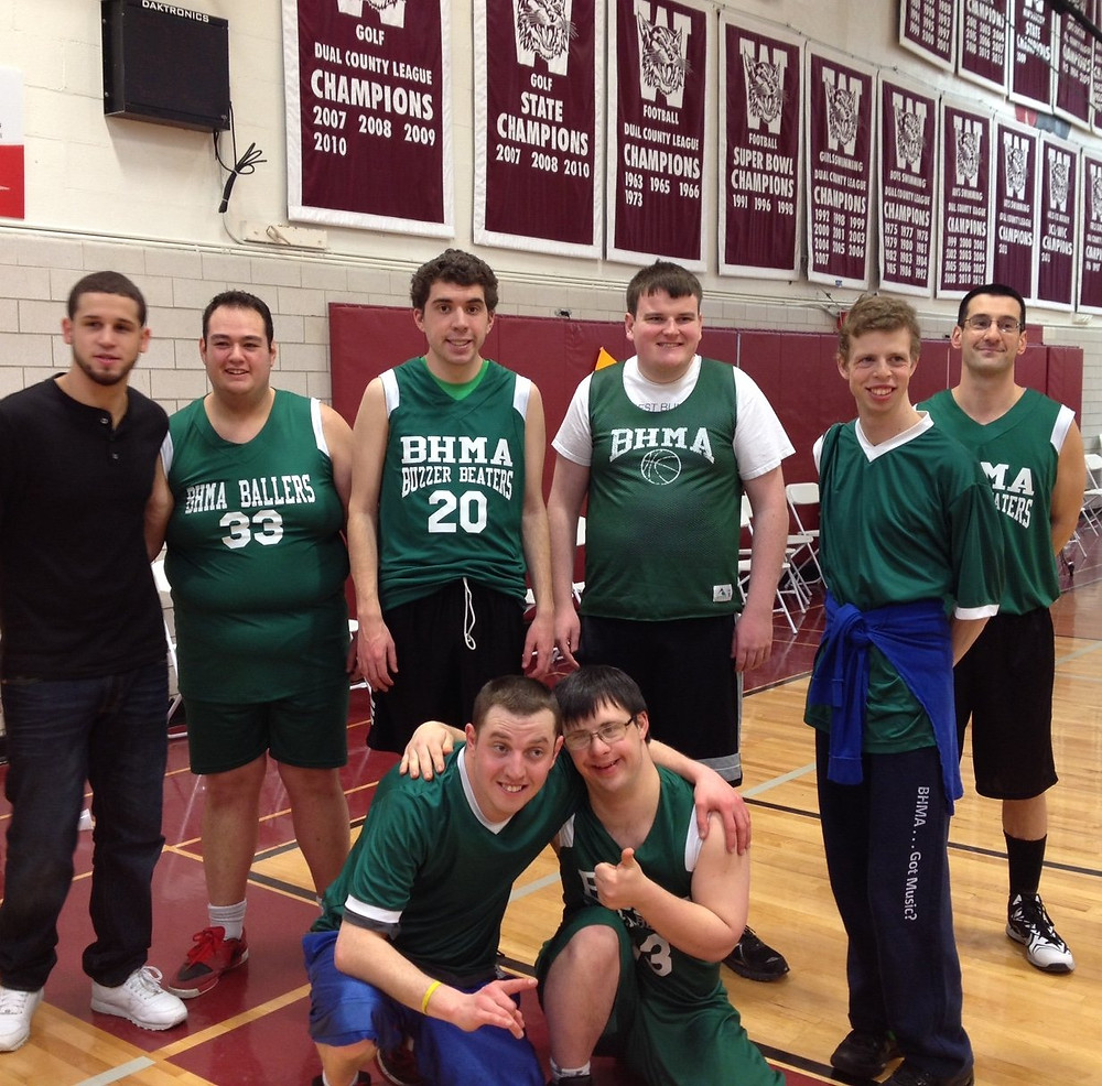 Image of the six members and two coaches of the BHMA Buzzer Beaters team posing for a photo in a gym.