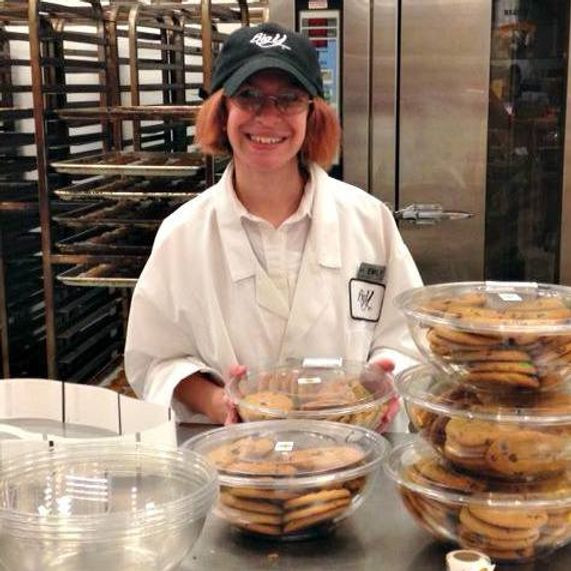Image of Emily Webster, wearing her Big Y uniform, smiling among containers of cookies in the Big Y bakery.