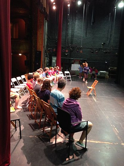 Image of Summer Program participants sitting in chairs on stage.