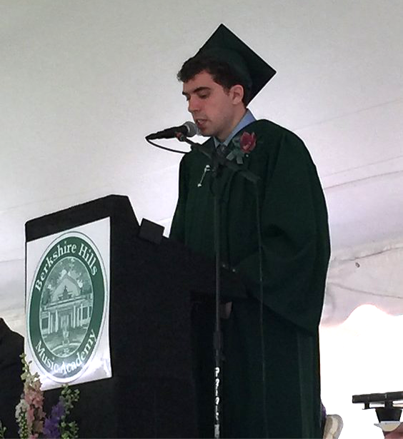 Image of Connor, wearing his green graduation cap and gown, speaking at the on-stage podium.