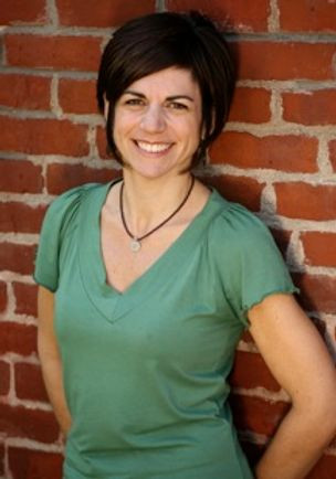 Image of Mary Ann Holmes, wearing a green v-neck shirt, posing against a brick wall.