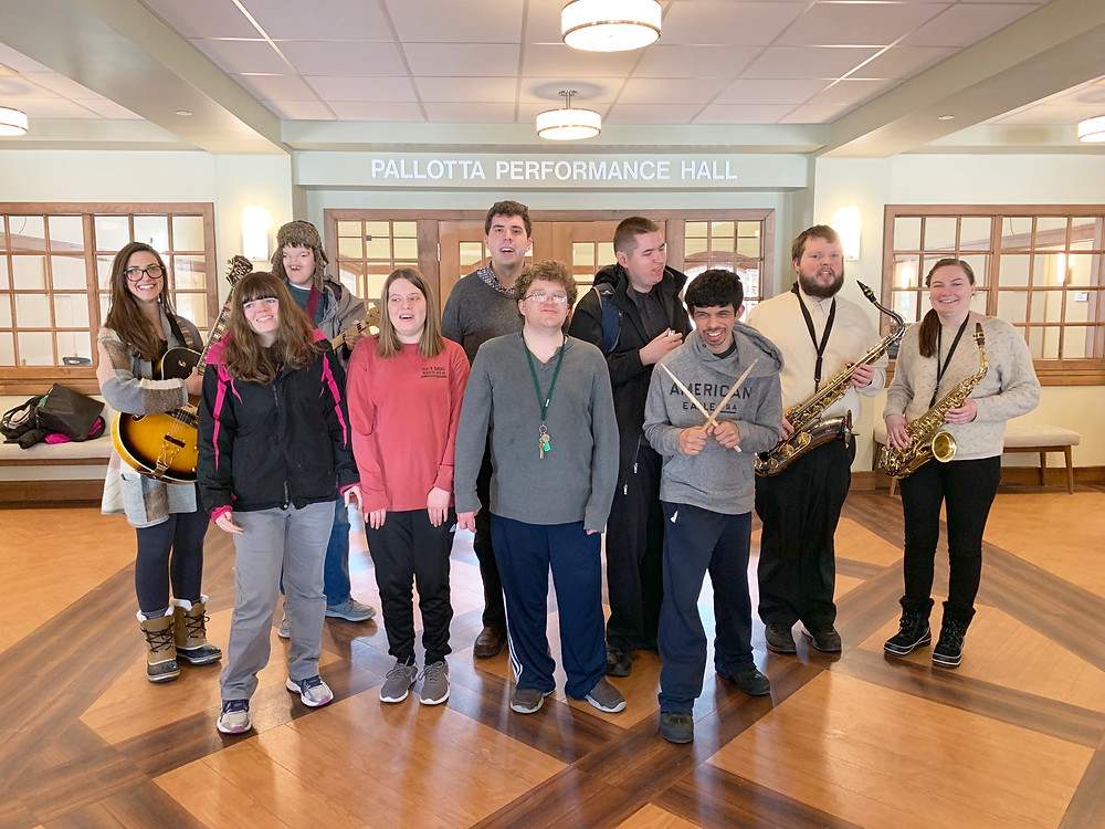 Image of the Jazz and Soul Ensemble, featuring ten individuals posing with instruments in the lobby of the Bernon Music Center.