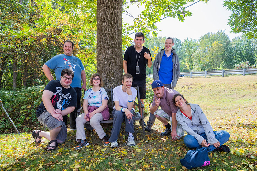 Photo of a group of eight BHMA students posing together around a tree in the springtime.
