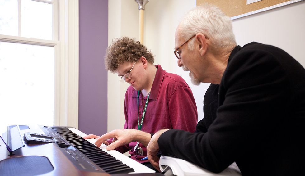 Photo of Music Instructor Tom Slowick guiding student Mark Palardy on the piano during a lesson in the purple studio.