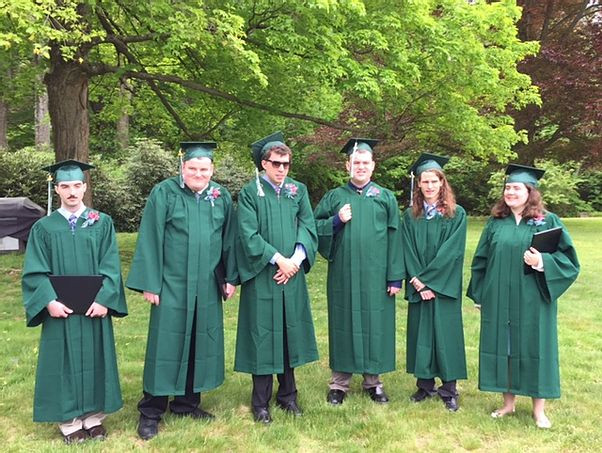 Image of the six members of BHMA's class of 2016, wearing their green graduation caps and gowns posing outside.