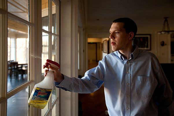 Image of Adam Shipp, wearing a blue long-sleeve button-down shirt, spraying Windex on a window to the porch.