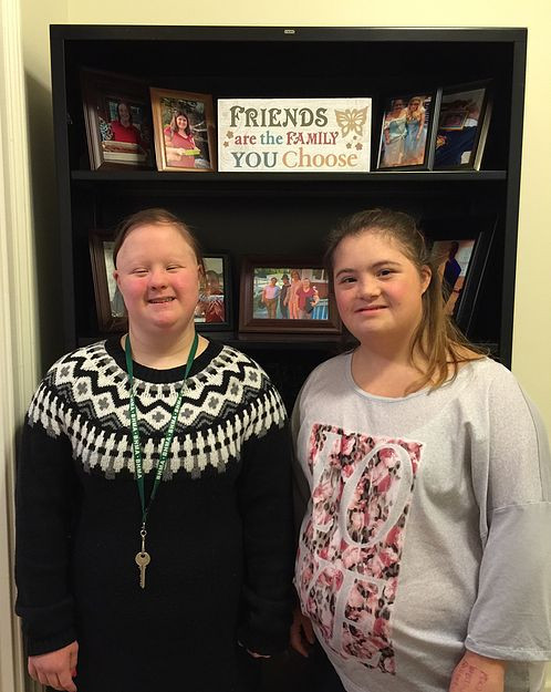 Image of Jordan Caira, right, and Emma Pignone, left, posing in front of a bookcase.