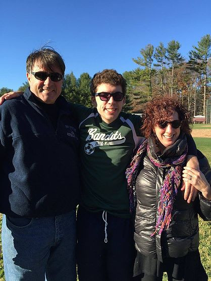 Image of Connor Thompson, center, posing with his family at the SOMA soccer tournament.
