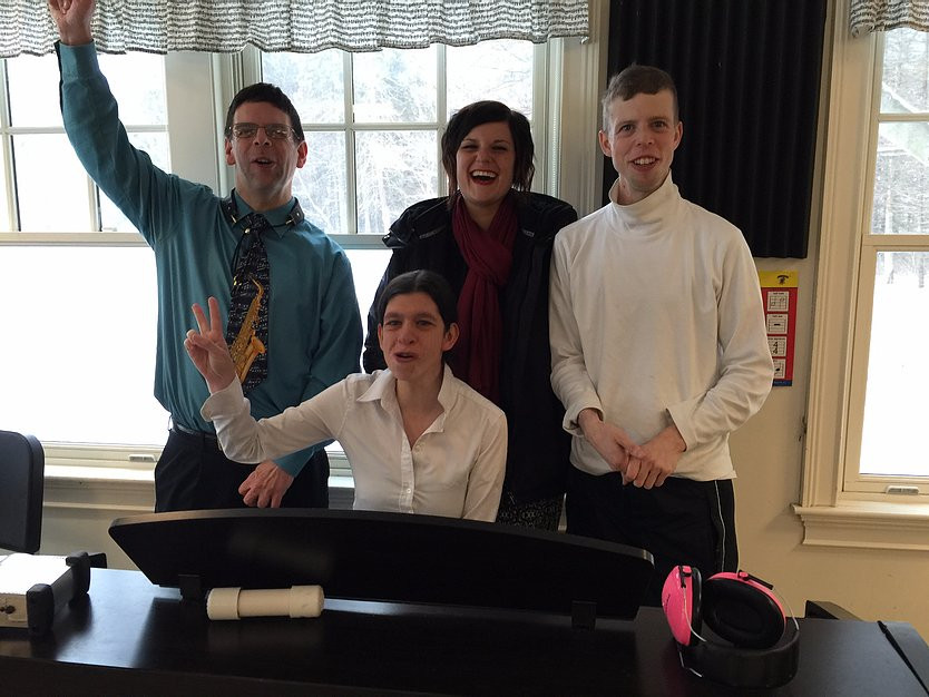 Image of John, Tori, Ewie Erasmus, and Tim Connor posing together around the piano in the ensemble room.