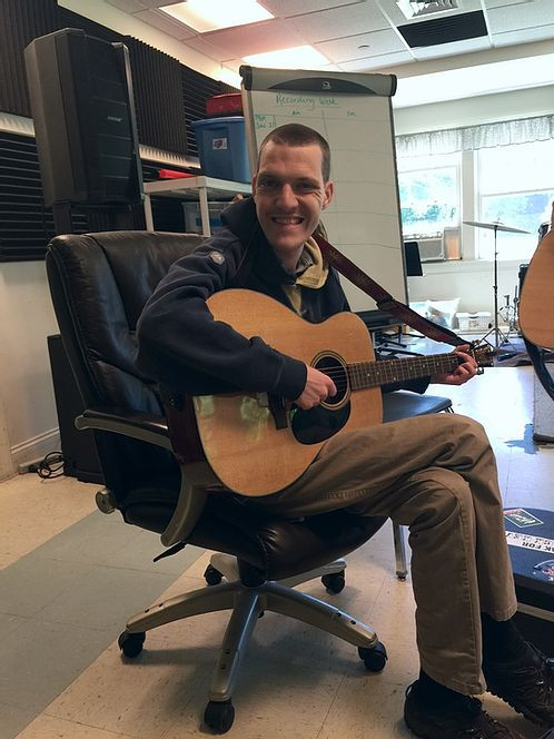 Image of Adam Shipp, wearing a blue hooded sweatshirt and khakis, sitting in an office chair as he smiles at the camera and strums an acoustic guitar.