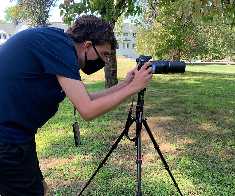 Photo of Connor Thompson, wearing black t-shirt, mask, and shorts, bending over to look at his camera on top of a tripod; green grass and trees are visible in the background.