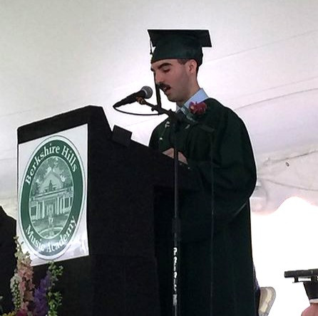 Image of Harry, wearing his green graduation cap and gown, speaking at the on-stage podium.