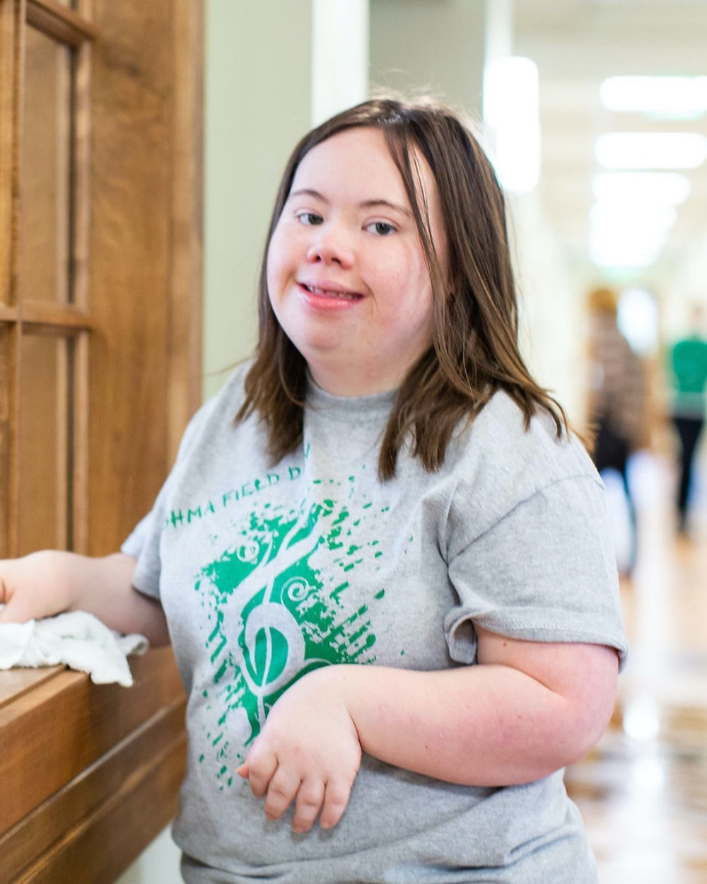 Photo of Jen Barrett, wearing a gray field day t-shirt, holding a white rag in her hands as she pauses while cleaning in the Bernon Music Center.