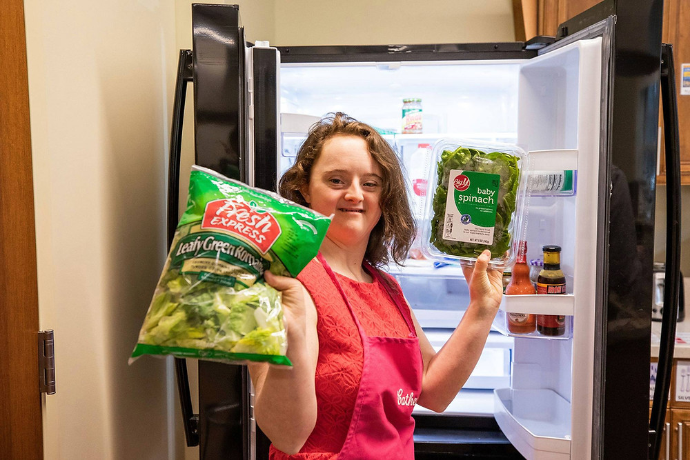 Image of Catherine Hackett holding up a package of lettuce in each hand; she stands before an open refrigerator.