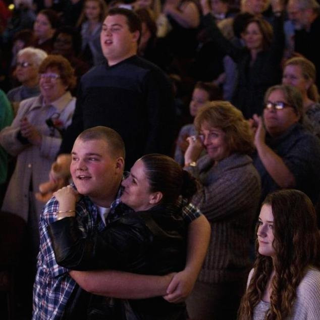 Image of the audience members embracing and wiping away tears following the showing of Lion King for sensitive audiences.