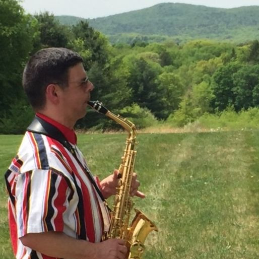 Image of John Libera, wearing a striped polo shirt and playing the saxophone, posing in BHMA's backyard during the summer.