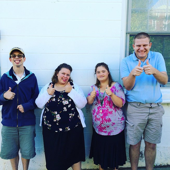 Image of Brett Beger, Carly Ziemba, Emma Pignone, and Brian Krutzler posing together against the side of a white building.