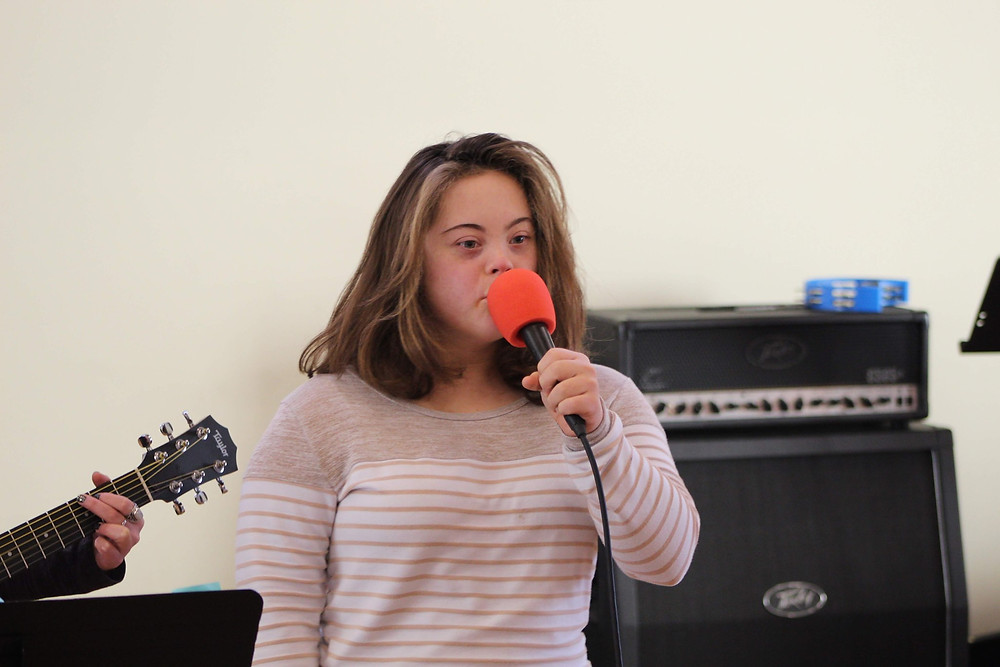 Picture of Karlie Forrest, wearing a tan and white striped shirt, holding a microphone with a large orange cover as she performs at Variety Hour.