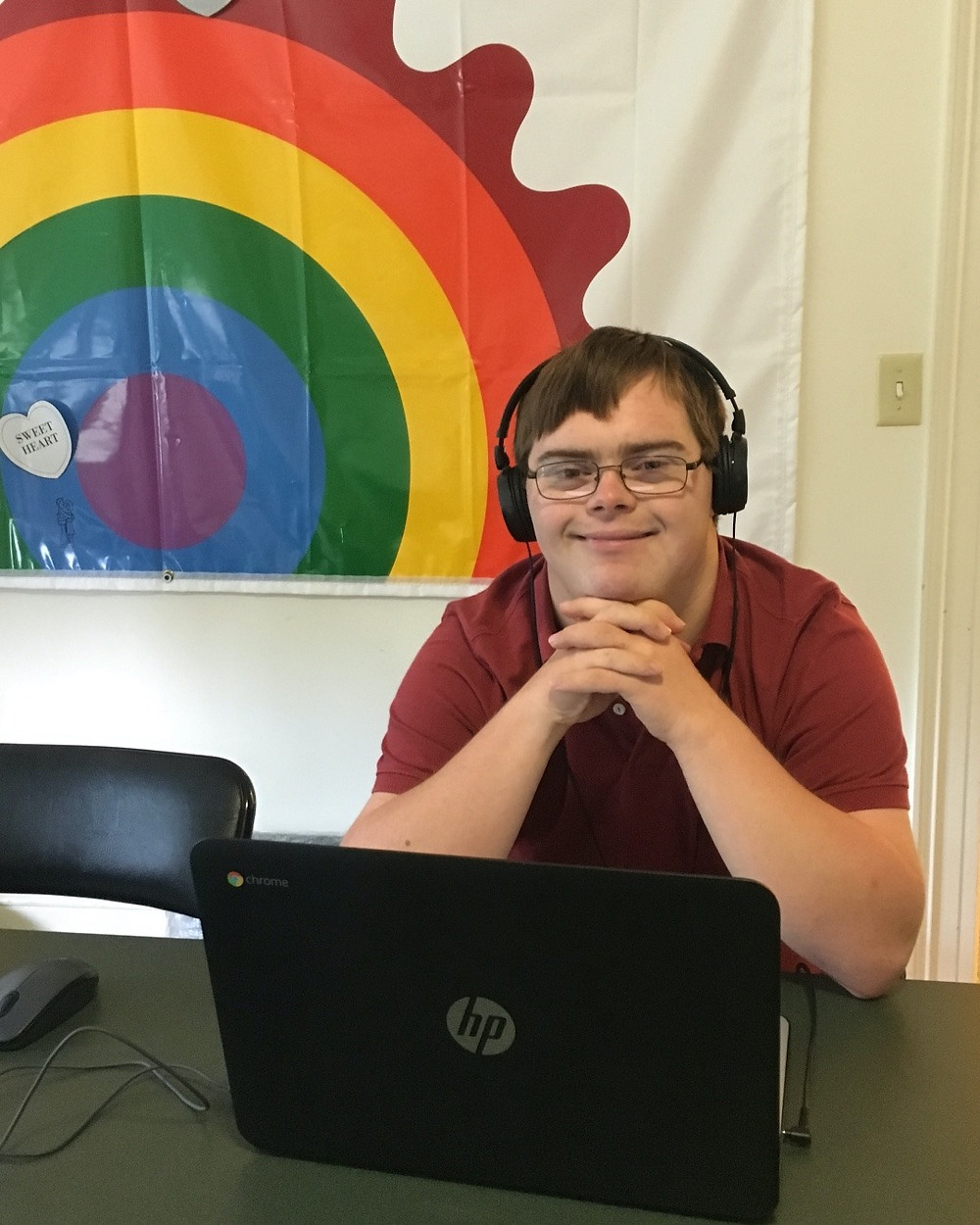 Image of William Duffy, wearing headphones and a red polo shirt, crossing his hands as he sits in front of an open laptop; the rainbow Circles tapestry is visible in the background.