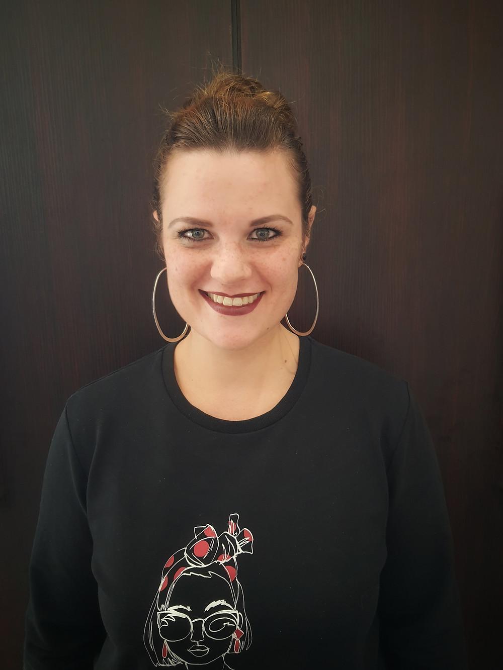 Headshot of Ewie Erasmus, wearing a black crewneck sweatshirt and hoop earrings; she stands against a black background.