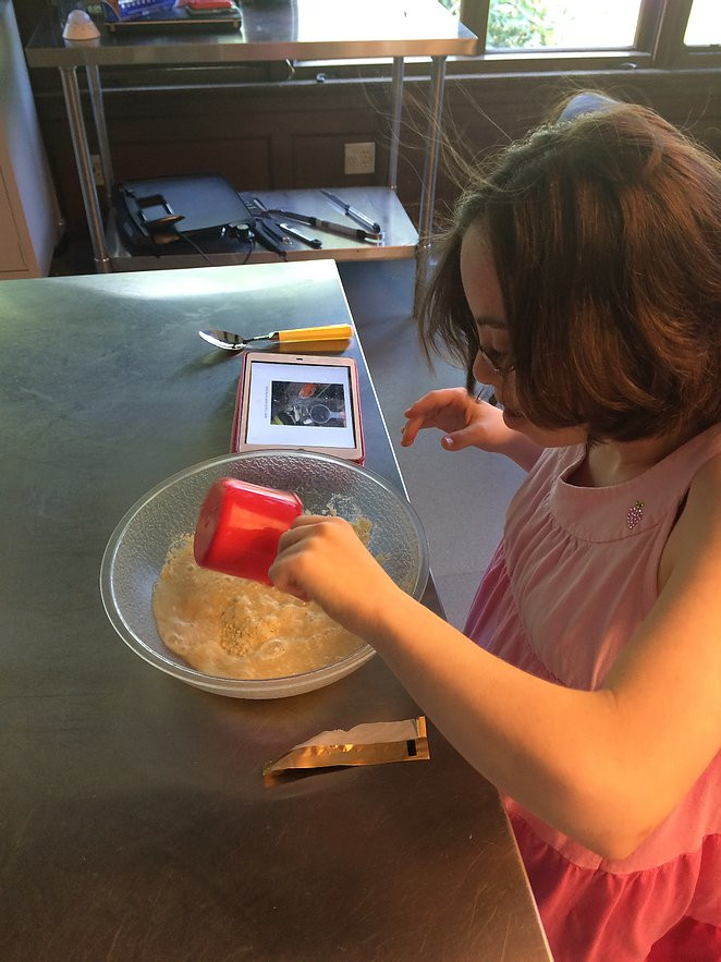 Image of Ilyse Ross measuring out a dry ingredient with the help of assistive technology.