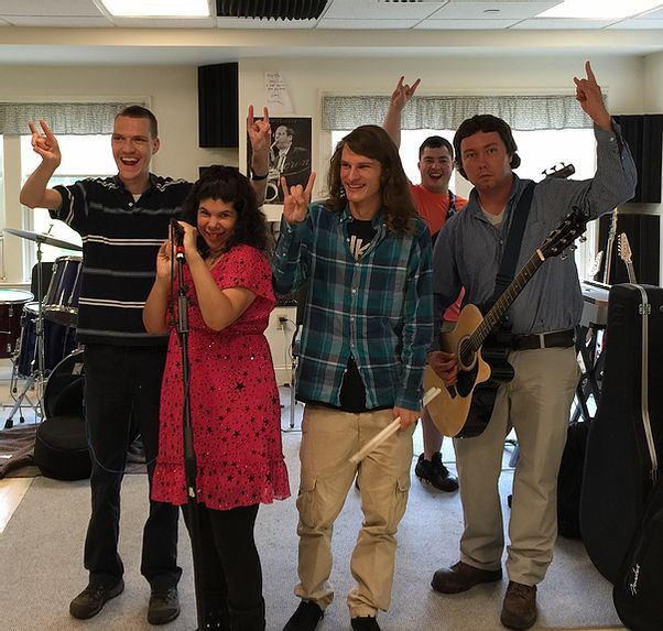 Image of Adam Shipp, left, posing with band members Ani, Sasha, Marco, and Dylan in the ensemble room.