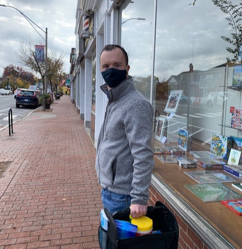 Photo of Graham Campbell, wearing a gray zip-up jacket, blue jeans, and mask, holding a cleaning bucket as he poses on a city sidewalk outside of the barbershop where he works.