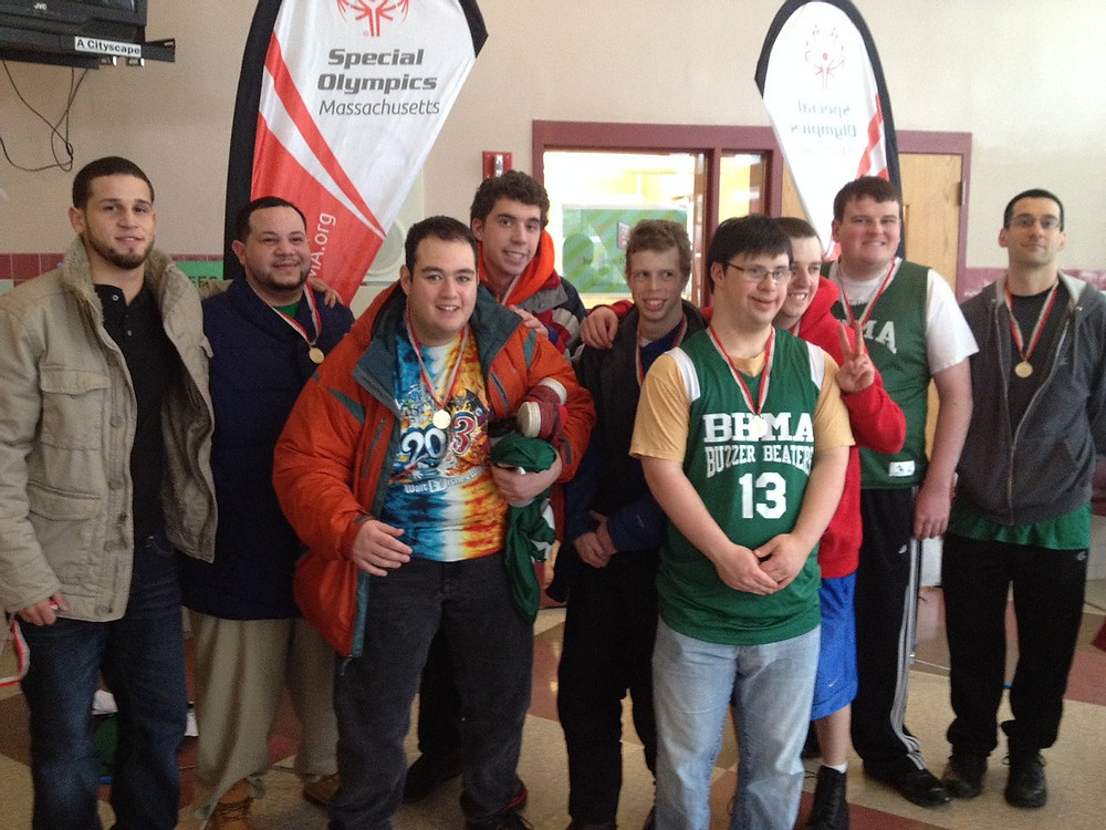 Image of the Buzzer Beaters team posing with their medals at the Special Olympics tournament.